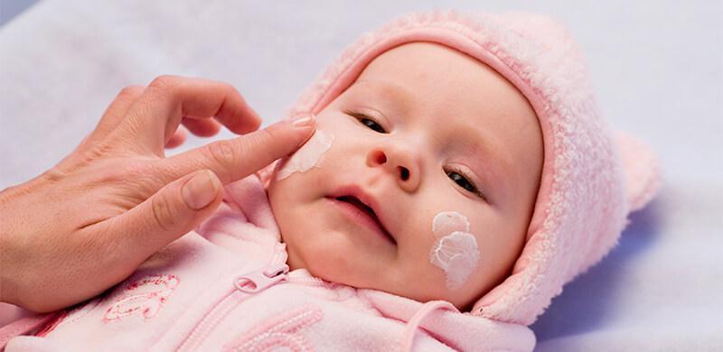 мама мажет щеки малыша кремом
