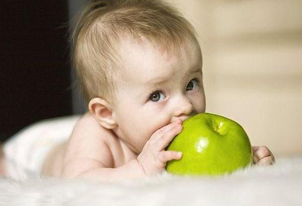 младенец с зеленым яблоком