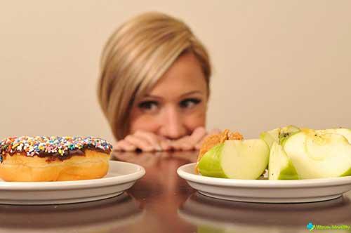 девушка выбирает между фруктами и десертом
