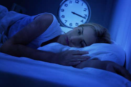 Девушка в кровати страдает бессонницей