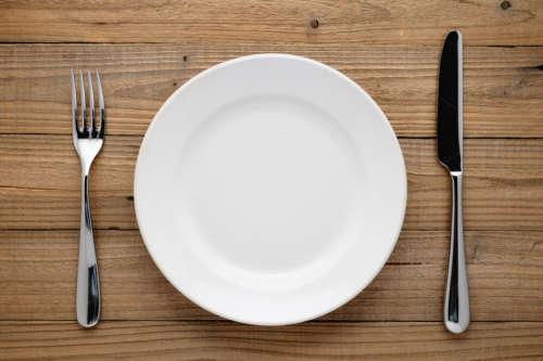Пустая тарелка с вилкой и ножом