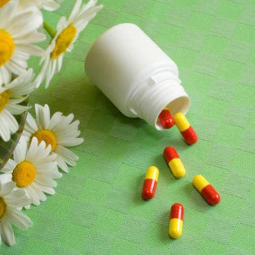 пузырёк с лекарствами рядом с маленьким букетом ромашек
