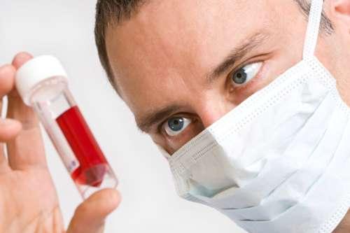 врач в маске держит пузырёк с жидкостью