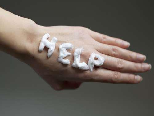 Женская рука с надписью Help кремом
