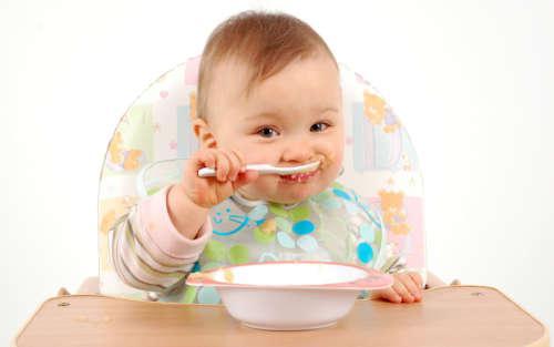 Малыш кушает ложкой