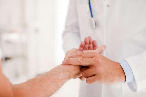 врач прощупывает пульс пациента на запястье