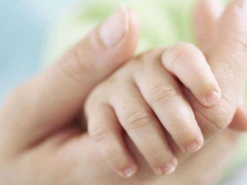 женская рука держит ручку малыша