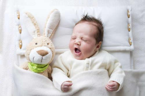 зевающий малыш и мягкая игрушка