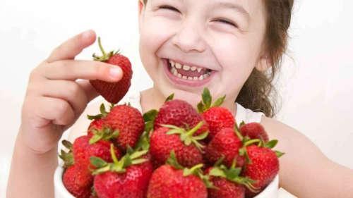 улыбающаяся девочка и чашка клубники