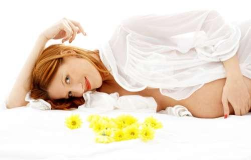 Беременная женщина лежит на постели, усыпанной ромашкой