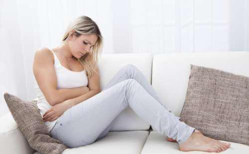 Девушка сидит на диване, обхватив руками живот
