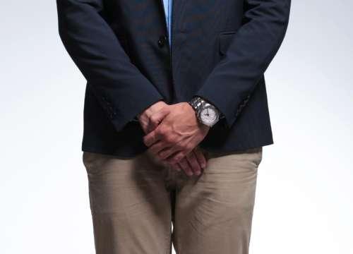 мужчина в костюме прикрывает половые органы
