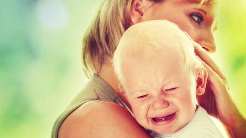 Плачующий ребёнок прижимается к женщине