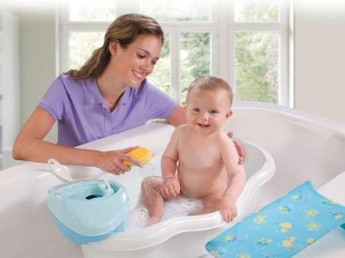 Девушка купает малыша в ванне