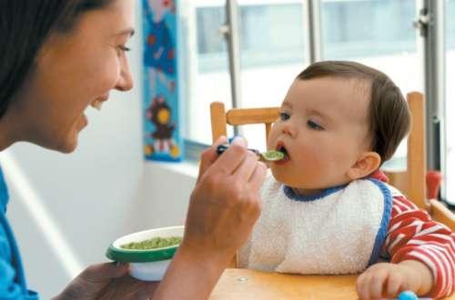 женщика кормит ребёнка с ложечки