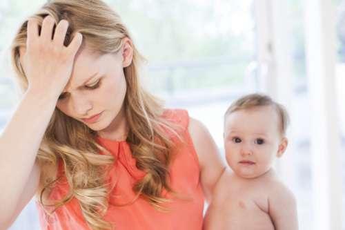 Девушка с ребёнком на руках держится за голову