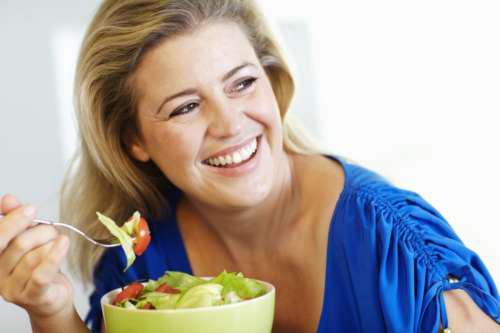 улыбающаяся женщина ест салат