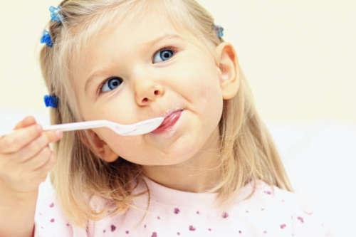 светловолосая девочка ест