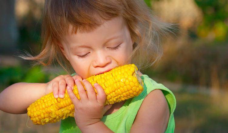 Ребенок ест кукурузу